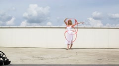 Dancer with a red ribbon posing on the roof for a photographer - stock footage