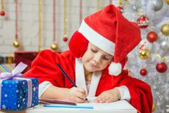 Girl with enthusiasm writes congratulations Christmas card - stock photo