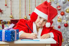 The girl with enthusiasm draws a Christmas card - stock photo