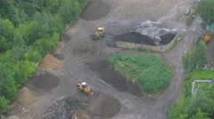 Excavator collects and loads the sand, near truck driving Stock Footage
