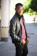 Black male fashion model posing in leather jacket - stock photo