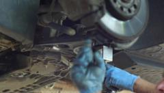 Worker secured with screws a piece of metal on the car hood - stock footage
