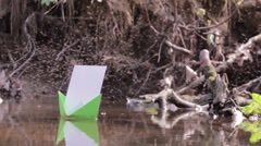 Green paper boat floating on water among thousands of midges Stock Footage