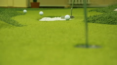 Hit the ball with a golf club to hit in the hole Stock Footage