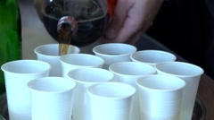 Man pours a glass of juice in plastic cups 23a Stock Footage