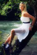 Stock Photo of A beautiful young woman in a radiant white summer dress posing in a forest