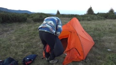 Tourist stow sleeping bagto a pouch in front of the tent 16a Stock Footage