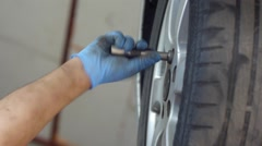 Auto mechanic working on a wheel from the machine damage 42 Stock Footage