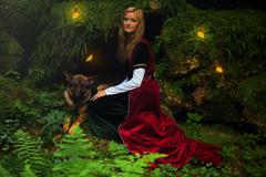 A beautiful woman fairy with long blonde hair in a historical gown, with dog - stock photo