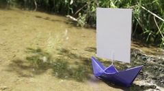 Blue paper boat that ran aground on the sandy shore 243 Stock Footage
