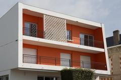 Stock Photo of Detail of modern apartments with balconies and red walls