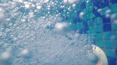 Underwater bubbles from pool water jet filling hose, underwater view of therm Stock Footage