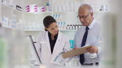 4K Workers in a chemist shop checking stock & discussing their work - stock footage