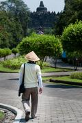 Man with straw hat walking towards Borobudur temple Stock Photos
