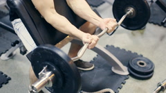 Man working arms at gym, he lifting bells and working his biceps, slow motion - stock footage