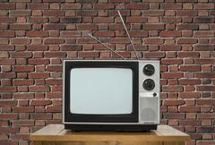 Old Television on Wood Table with Brick Wall - stock photo