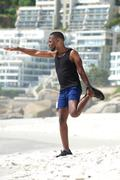 Active man stretching muscles at the beach - stock photo