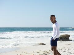 Handsome young man standing alone at the beach Stock Photos