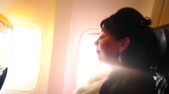 Profile of woman in airplane with bright light from portholes Stock Footage