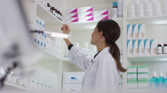4K Worker in a pharmacy putting a bottle of natural medicine onto shop counter Stock Footage