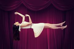 Composite image of girl in white dress floating in air Stock Photos