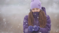 Little girl hat catching snowflakes in winter park. Stock Footage