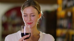 4K Portrait of woman testing the quality of a glass of wine in specialist wine s - stock footage