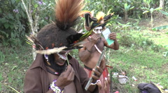 Papuan men painting their faces in Papua New Guinea Stock Footage