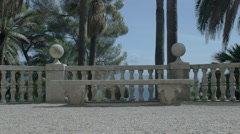 Stock Video Footage of Moving towards Luxurious Marble Bench under Palm Trees - 25FPS PAL