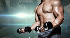 Composite image of mid section of a bodybuilder with dumbbells - stock photo