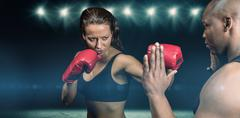 Composite image of female boxer practicing with trainer Kuvituskuvat