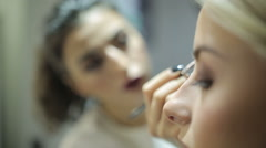 Stylist making make-up of a beautiful young model. Stock Footage