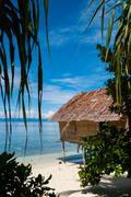 Nipa Hut on stilts at a Beautiful white sand Beach in front of the ocean - stock photo