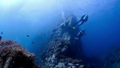 Divers drifting next to large pinnacle - stock footage