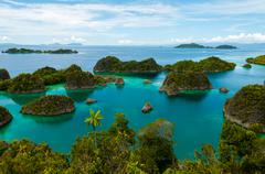 Many small green Islands belonging to Fam Island in the sea of Raja Ampat, Papua - stock photo