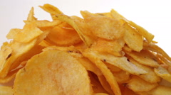 Potato chips heap rotating over white background, macro view Stock Footage
