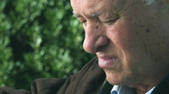 outdoor closeup portrait of worried and pensive 70s old man - stock footage