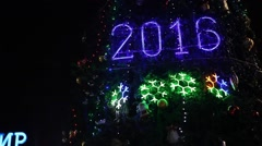 Illuminated 2016 new year sign on decorated Christmas tree Stock Footage