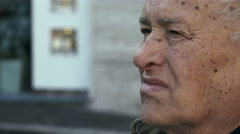 Pensive worried old man in the city: elder caucasian 70's in urban context  Stock Footage