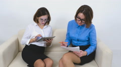 Two businesswomen using tablet computer and verifies the documents Stock Footage