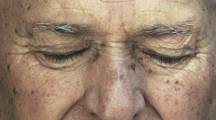 extreme closeup footage of old caucasian man opening eyes: 70s wrinkled elder - stock footage