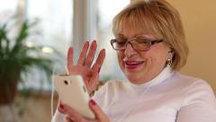 Woman with white smartphone speaks smiling, laughs and gesticulates Stock Footage