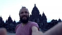 Man taking selfie photo by Prambanan temple, super slow motion Stock Footage