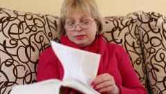 Woman sits on a couch and flips through the pages of big book - stock footage