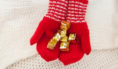 Female hands in winter red gloves with christmas gift box - stock photo