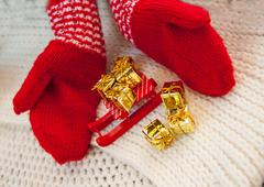 red knitted mittens sled and golden gifts. The concept of Christmas - stock photo