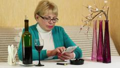 Woman sits at the table, drinks red wine and uses smartphone Stock Footage