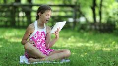 Beautiful girl with tablet computer sits on the grass in garden Stock Footage