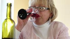 Woman drinks red wine. Depressed senior woman with bottle of wine Stock Footage