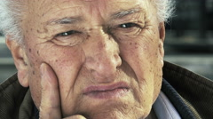 wrinkled caucasian 70s old man sitting alone and pensive: closeup portrait  - stock footage